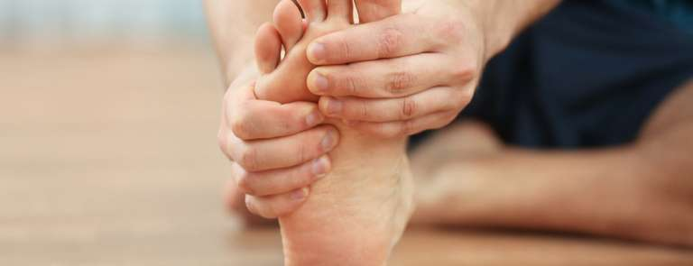 man with foot cramp