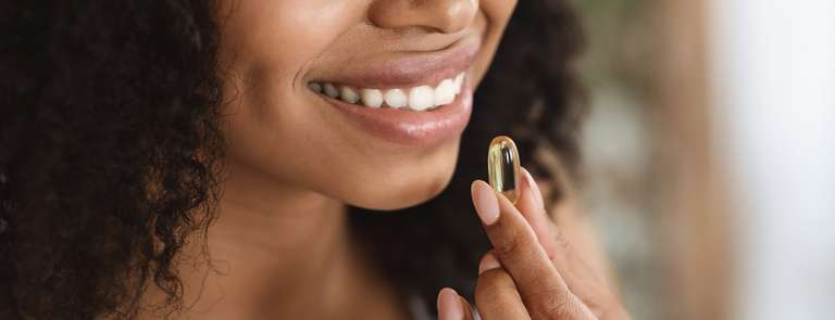closeup of woman smiling taking omega 3 supplement