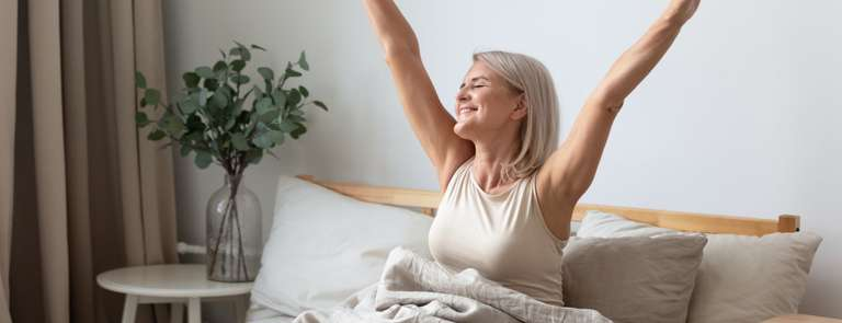 older woman waking up happy