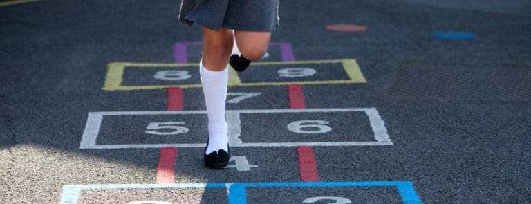 A girl playing hopscotch in a playground