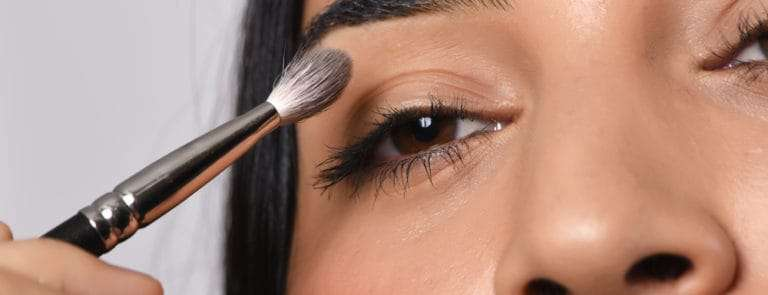 A women applying make up to just above her eye