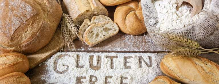 Gluten free spelt out in flour with bread loaves around it