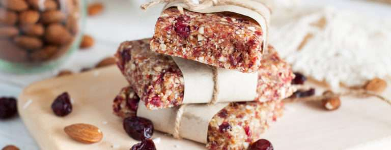 Three protein oat bars with cranberries and nuts in, piled on top of each other. They are on top of a chopping board with nuts and fruit scattered around.
