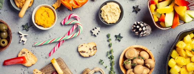 An array of vegetarian snacks such as hummus, garlic mushrooms, rye bread, oranges and candy canes on a table.