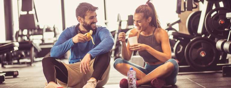 two people sat in the gym drinking pre-workout