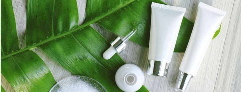 cosmetic bottles on background of big green leaf