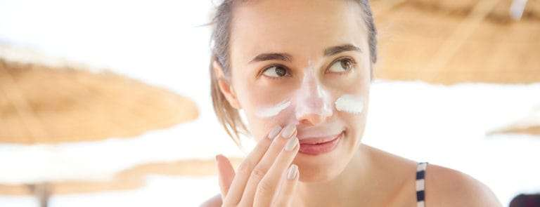 Woman at beach applying sun protection to face