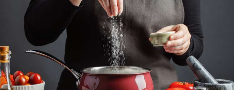 person putting salt into a their cooking