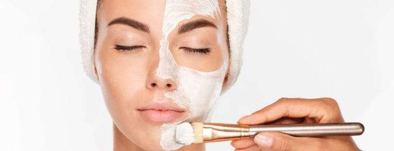 woman eyes closed with a head towel on with half her face being covered in cream