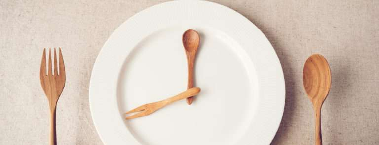 A plate with a spoon and fork resembeling the hands of a clock and two hands holding a fork in one hand and a spoon in the other.