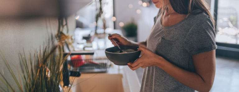 Girl standing in kitchen over the sink with a bowl of food