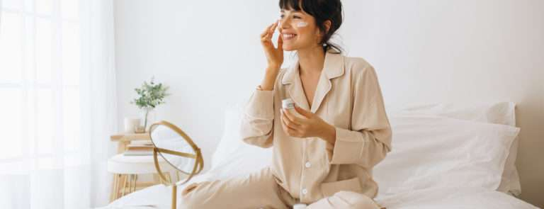 A lady sitting on her bed, with a face mask on with a mirror and skincare products beside her.