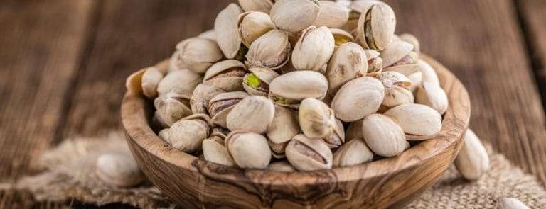 Pistachios nuts in wooden bowl.