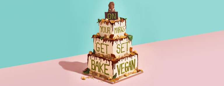 """3-tier vegan banana cake with cream icing and chocolate drizzle, green writing """"On your marks, get set, bake vegan"""", decorated with leaves, acorns and a squirrel at the top"""