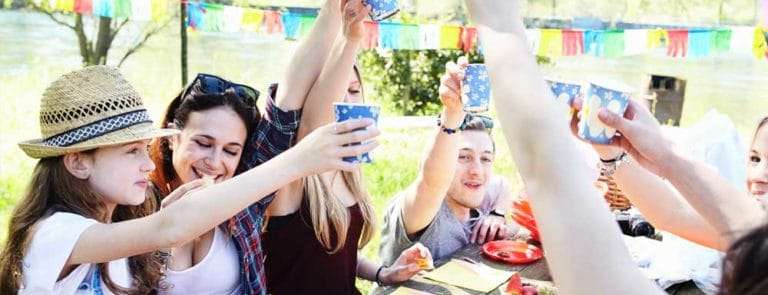 Group of friends having a picnic on a bench with bright napkins and cups