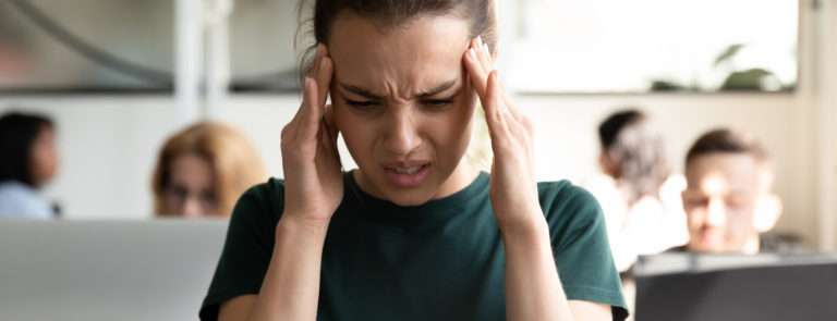 A lady looking distressed with both hands on her head.