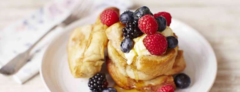 A plate of french toast with fruit and syrup