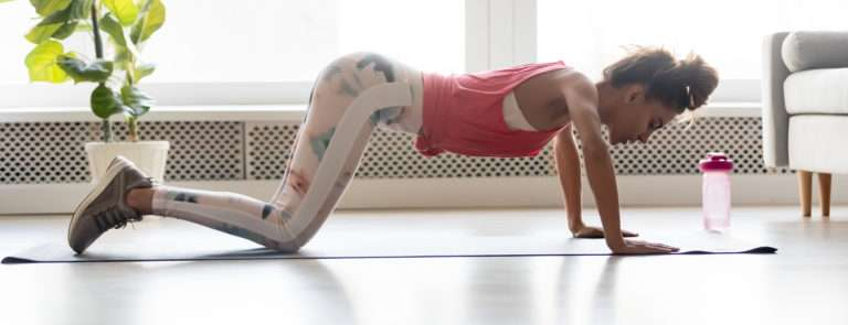 woman doing a push up at home to strengthen her upper body