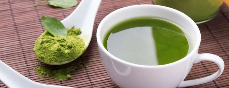 close up of green tea with spoon of powder