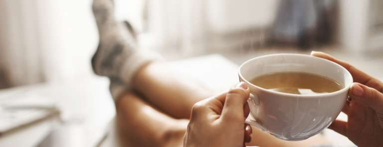 closeup of woman holding tea and relaxing at home