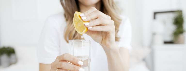 woman squeezing lemon into water glass