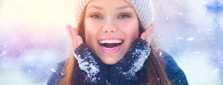 Girl touching her face skin and laughing, in the snow