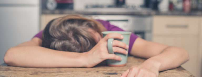A lady asleep at her desk whilst holding a mug in one hand.