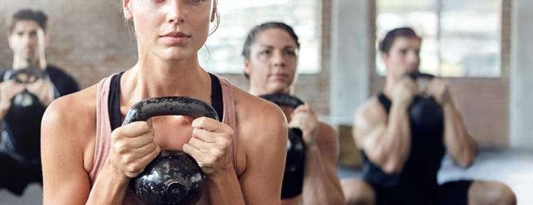 People holding kettlebells in gym