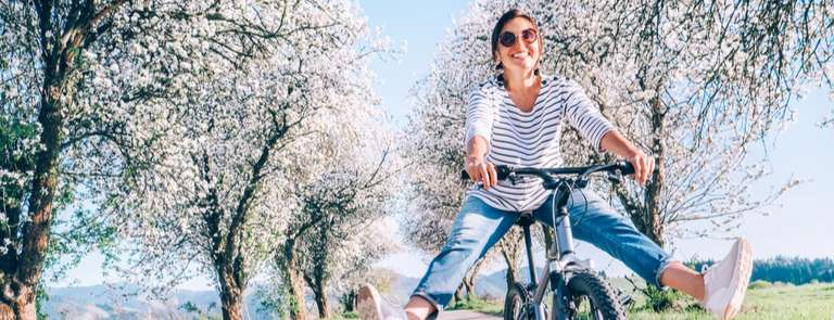 woman in a spring meadow riding a bicycle