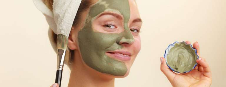 A lady applying a green clay mask with a brush on half of her face and a towel on her head.