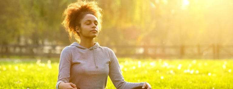 Woman sitting cross-legged on a grassed area with the sun shining brightly