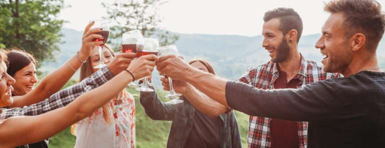 A group of friends, cheersing with wine glasses in a circle, outdoors.