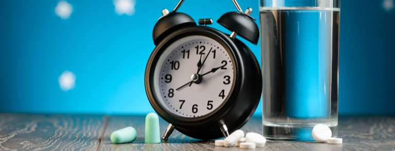 sleeping tablets next to alarm clock and glass of water