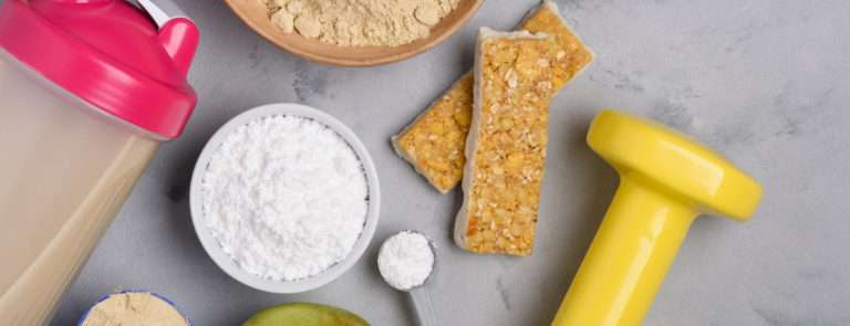 A yellow handheld weight surrounded by two bowls of protein powder, some protein bars and an apple.