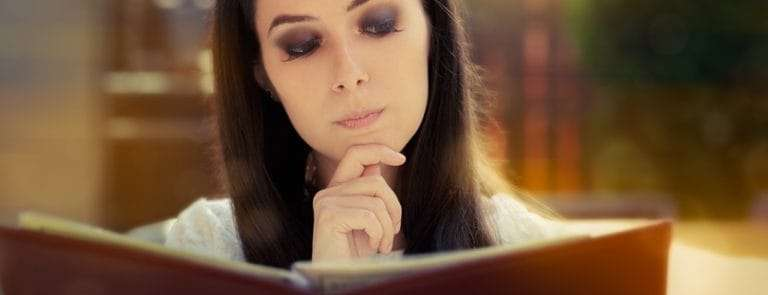 A women reading a book and pondering