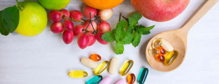 multivitamins in wooden spoon with selection of fresh fruit
