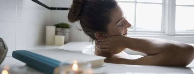 woman bathing with a book and candle