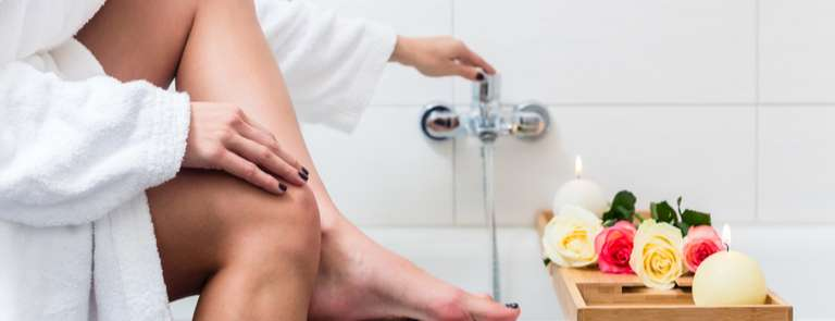 women running a bath with candles and natural scents