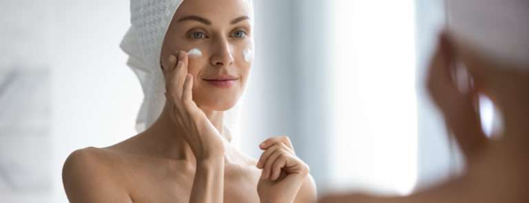 A lady with a towel around her body and another around her head, putting cream on her face in a mirror.
