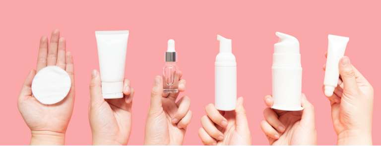 female hands holding up various beauty products
