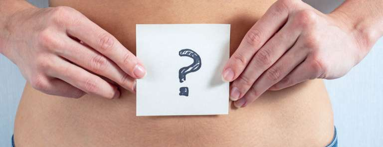 woman holding question mark paper over belly button