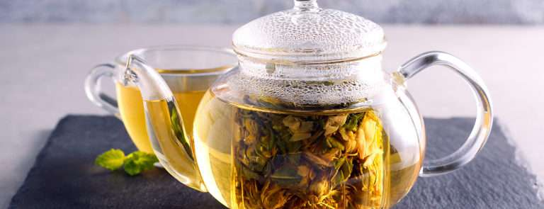 A glass teapot with fennel tea bag in and boiled water.