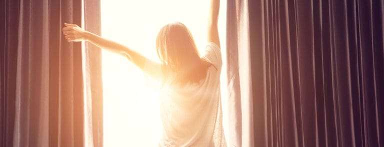 Woman stretching by window after a good nights sleep