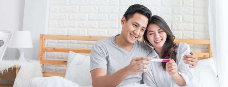 couple happy looking at pregnancy test