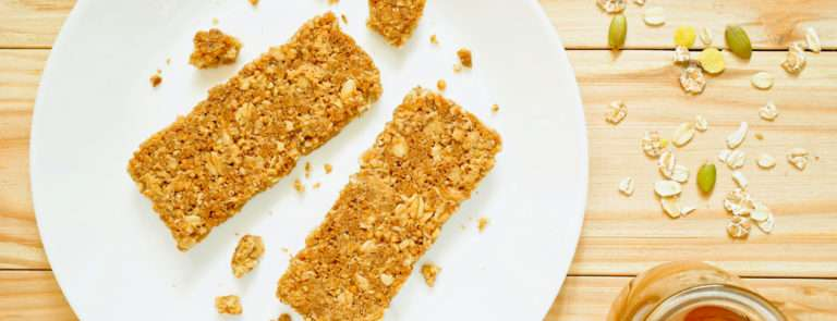 two oat flapjacks on a plate next to a pot of honey and some nuts and seeds