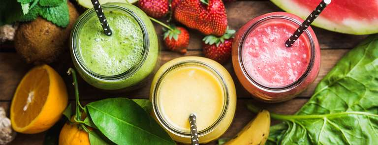 selection of fruit smoothies with fresh cut fruit
