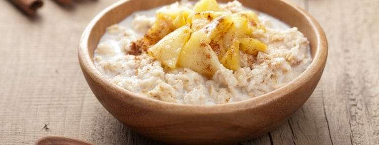 Porridge with apple and cinnamon in a wooden bowl against a wooden background