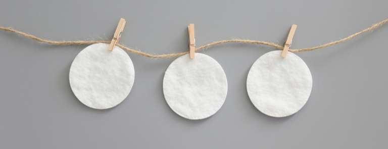 three cotton pads hanging on natural string with wooden pegs