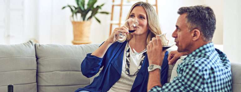 man and woman drinking a glass of red wine sat on a sofa