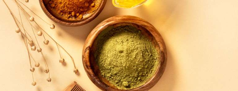 henna powder in a wooden bowl next to a wooden comb
